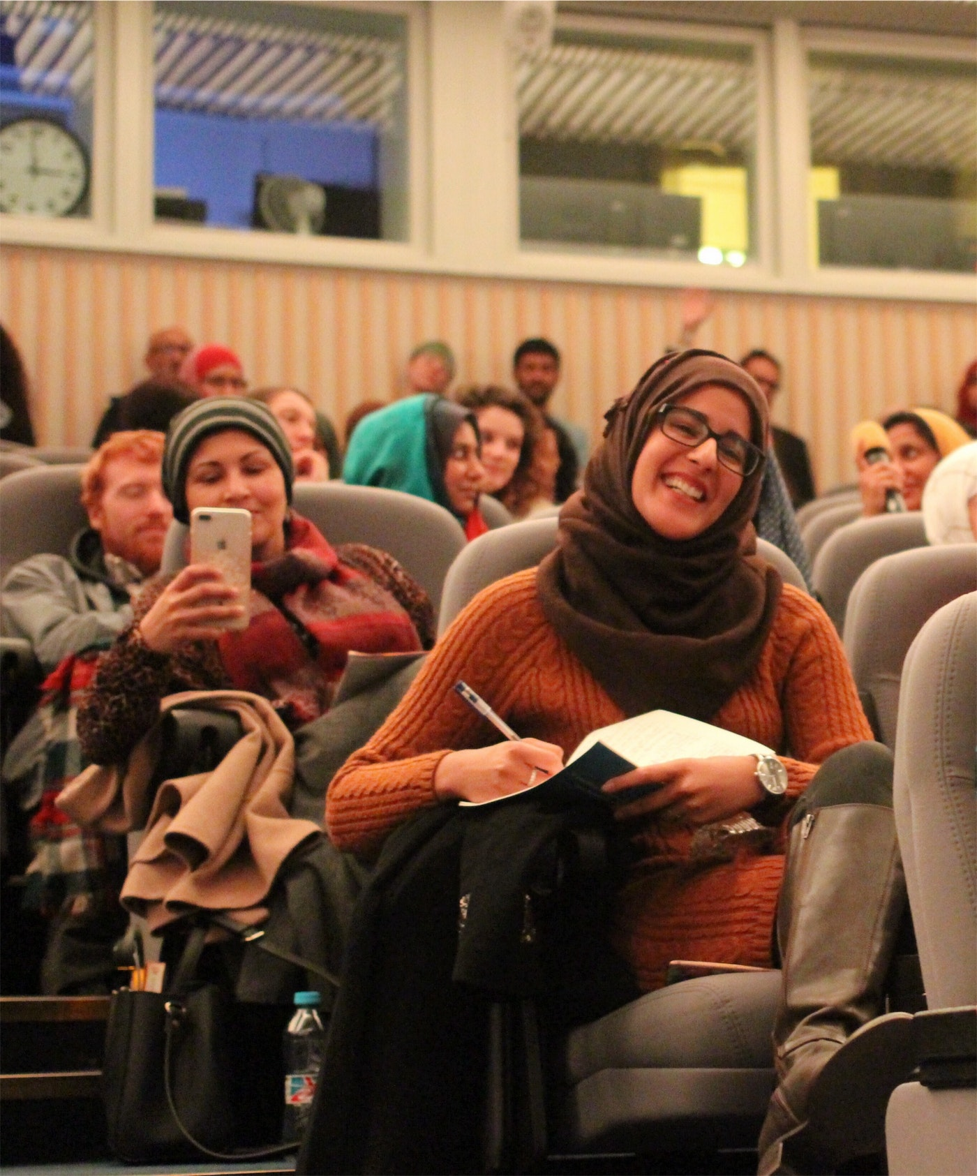woman in a brown hijab, orange jumper and glasses laughing with a pen and notebook and sitting in a lecture theatre surrounded by other people.