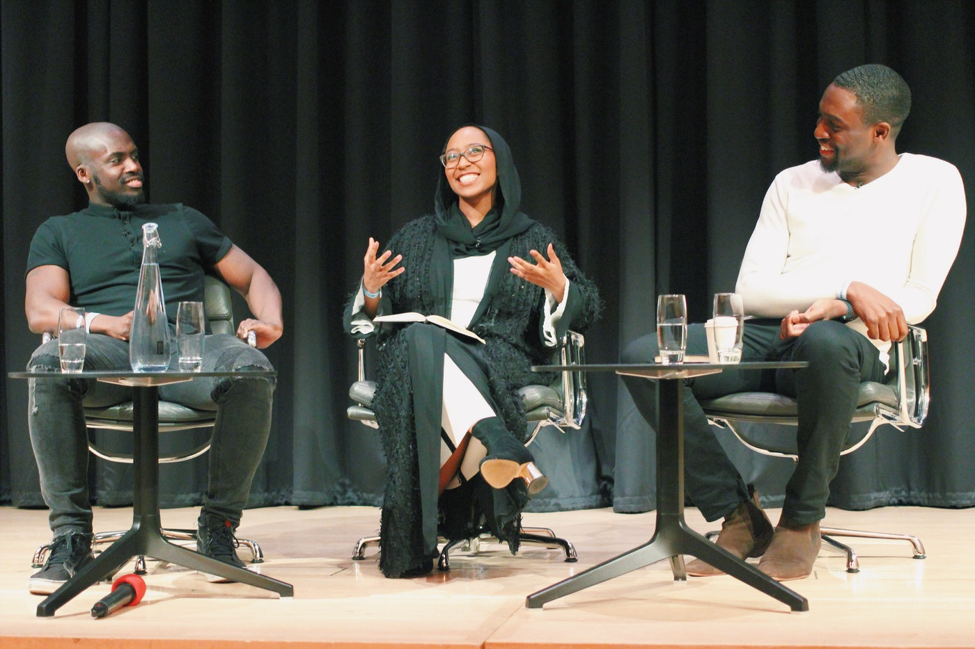 3 people sitting down on a stage speaking